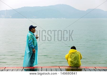 NANTOU TAIWAN - SEPTEMBER 04: An old couple relaxing by the famous Sun Moon lake on a foogy day on September 04th 2014 in Nantou