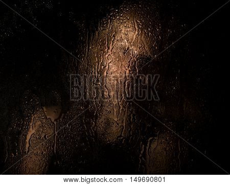 Smooth portrait of sexy model, posing behind transparent glass covered by water drops. young melancholy and sad woman portrait.