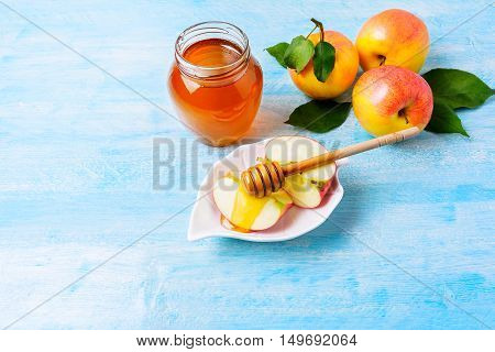Apple slices with honey on blue wooden background. Rosh hashanah concept. Jewesh new year symbols. Copy space.