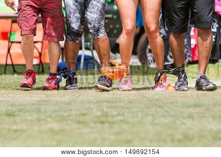 ATLANTA, GA - JULY 2016: The legs of four young adults walk in unison in a five-legged race as part of the kid's games played by adult teams at the Atlanta Field Day in the Old Fourth Ward Park in Atlanta GA on July 16 2016.