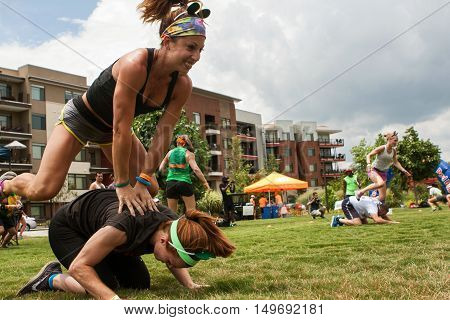 ATLANTA, GA - JULY 2016: Two women play leap frog one of many children's games played by teams at the Atlanta Field Day event at the Old Fourth Ward Park in Atlanta GA on July 16 2016.