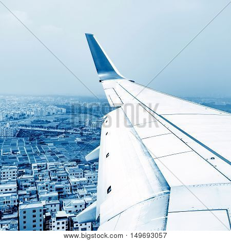 The airplane flies high above the city and the wing shines in the sun.