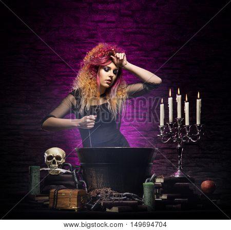Young and beautiful witch in a dungeon. Halloween concept.