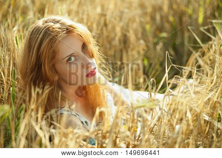 Young redhead girl lying in a meadow