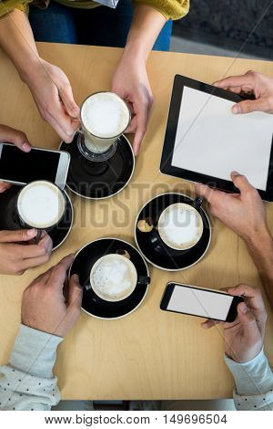 Friends using mobile phone and digital tablet while having cup of coffee in caf\x92\xA9