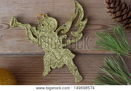 golden Christmas cherub and Christmas tree branches on wooden table