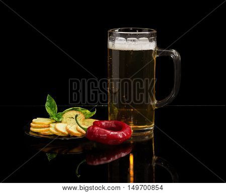 Beer glassware with lager beer rusks with pesto sauce flavor and twig of basil on a saucer and chili pepper on a dark reflective background