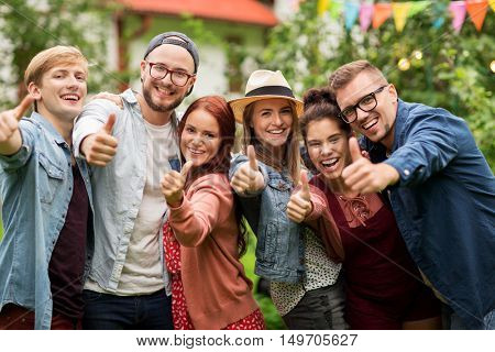 leisure, holidays, reunion, people and friendship concept - happy teenage friends showing thumbs up at summer garden party