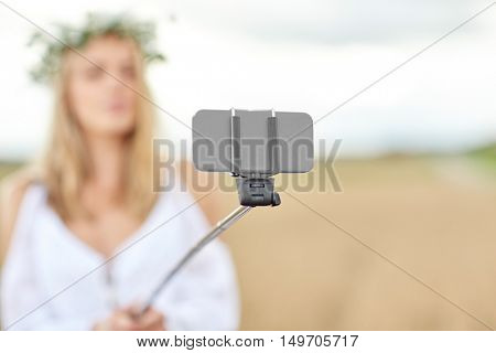 technology, summer holidays, vacation and people concept - close up of young woman in wreath of flowers taking picture by smartphone selfie stick on cereal field