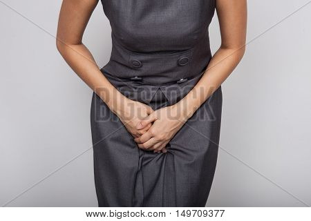 Close up of a woman with hands holding her crotch