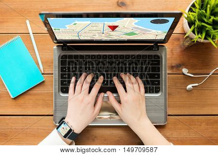 navigation, location, people and technology concept - close up of woman or student typing on laptop computer with gps navigator map on screen, notebook and earphones on wooden table