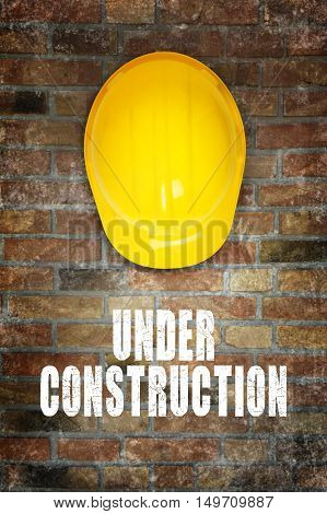 Under construction. Yellow safety helmet on brick wall background.