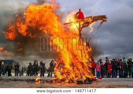 Saint-Petersburg Russia - February 22 2015: Feast Maslenitsa on Vasilyevsky Island. Burning doll - the flames destroyed almost the entire doll. Spectators take pictures of what is happening.