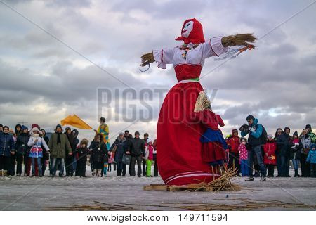 Saint-Petersburg Russia - February 22 2015: Feast Maslenitsa on Vasilyevsky Island. Burning doll - a doll has been prepared the audience are at a safe distance.