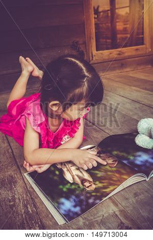 Closeup handsome asian girl smiling and reading picture album lying on wooden floor with bright sunlight outdoor at home. Children read and study education concept. Vintage tone effect.