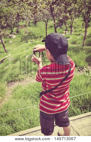 Back view of happy asian boy with camera at national park . Child taking photographs by camera outdoors with bright sunlight at the daytime travel on vacation. Vintage effect and cream tone.