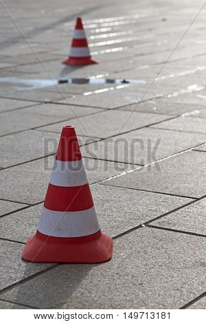 two traffic cones with red and white stripes on a paved road with a puddle vertical copy space selected focus narrow depth of field