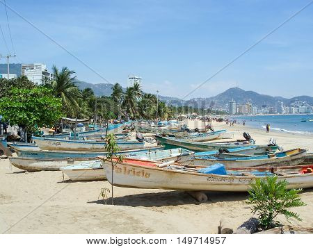 ACAPULCO MEXICO - MARCH 11 2006 : A group of boats lined up on the beach with people in the background in Acapulco Mexico.