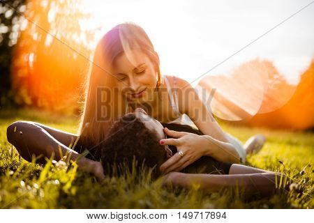 Young multi racial couple hugging in nature on grass - woman looking to his eyes