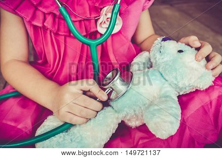 Child Playing Doctor Or Nurse With Plush Toy Bear At Home. Vintage Tone Effect.