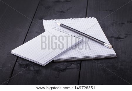 Pencil and notepad with spiral on black wooden textured table. Side view.