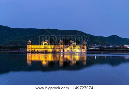 Illuminated Jal Mahal palace at night in Jaipur, India. Popular landmark surrounded by water. Mountains at the background