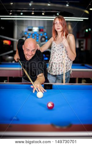 Beautiful young couple flirting while playing snooker