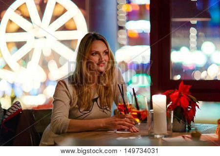 beautiful woman drinking champagne cocktail after work in an indoor cafe and restaurant in London, United Kingdom. Christmas market with ferris wheel and lights on background. Happy girl dreaming on evening or night.