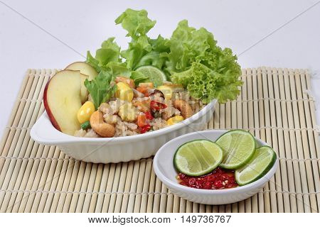 Fried  rice with mixed vegetable as ginkgo,tofu,corn,lentils,tomato,carrot,taro,mushroom,Lettuce,cashew nut,apple,green lemon and red chili  served with side dish as red chili and green lemon in tofu sauce for Chinese vegetable festival call