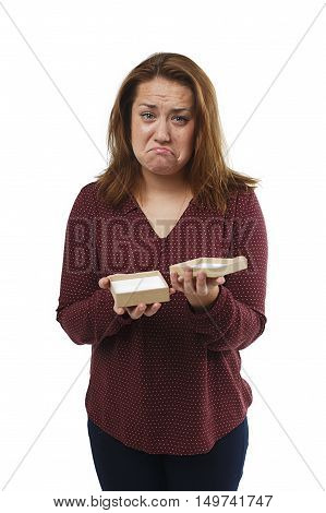 disappointed girl with gift box in hands. dissatisfied woman opening gift. the concept of deceived expectations. isolated on white background poster
