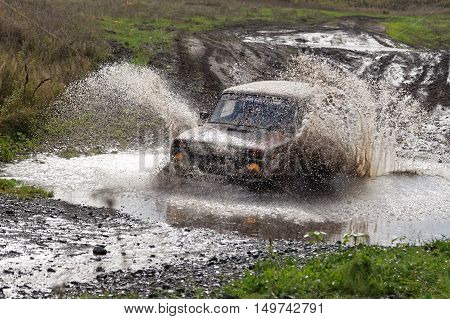 Rally Car Boosts Water Hurdle Surrounded By Splashes.