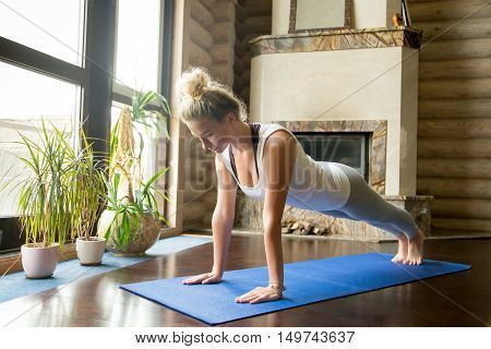 Full length portrait of attractive young woman working out at home in living room, doing yoga or pilates exercise on blue mat, standing in plank pose phalankasana