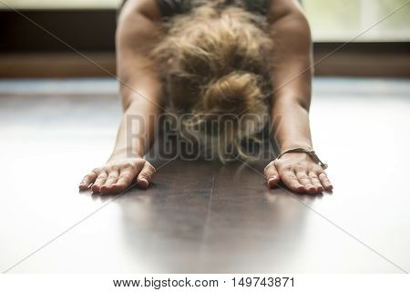 Attractive young woman working out at home, doing yoga exercise on blue mat, lying in Balasana, Child Pose, Ardha-Kurmasana Half Tortoise Pose . Close-up, focus on hands