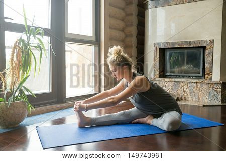 Full length portrait of attractive young woman working out at home in living room, doing yoga or pilates exercise on blue mat, sitting in Janu Sirsasana, head-to-knee forward bend posture