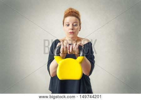 Surprised woman lifting weights. Selective focus on hands with kettlebell.