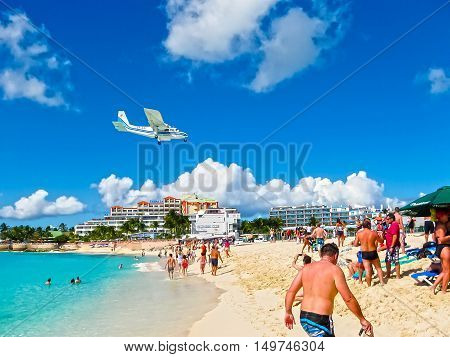 Philipsburg, Sint Maarten, Netherlands - February 13, 2013: The beach at Maho Bay is one of the world's premier planespotting destinations. Airplanes landing at the Princess Juliana Airport fly over beachgoers.