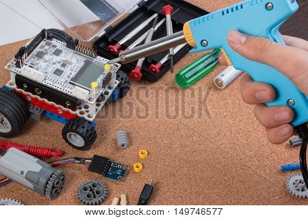 Hand Holding Soldering Iron Tool Assembling Robot With Microcontroller.