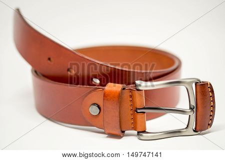 Brown leather belt and silver buckle on white background.