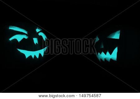 Two Blue Carved Face Of Pumpkin Glowing On Halloween Black Background