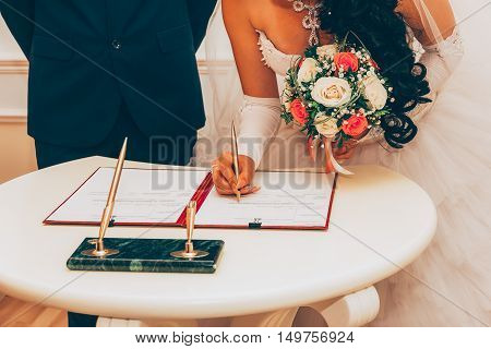 Wedding. Registration Of Marriage The Bride With A Bouquet Of Flowers Signed A Marriage Contract A Golden Pen Selective Focus. Tinted Image