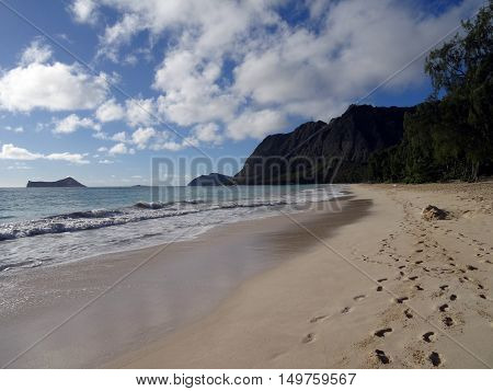 foot prints in the sand with Gentle wave lap on Waimanalo Beach looking towards Rabbit island and Rock island on a nice day Oahu Hawaii. July 2016.