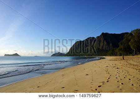 Gentle wave lap on Waimanalo Beach with foot prints in the sand looking towards Rabbit island and Rock island on a nice day Oahu Hawaii. June 2016.