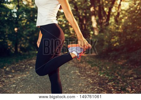 Woman stretching legs before running in the park