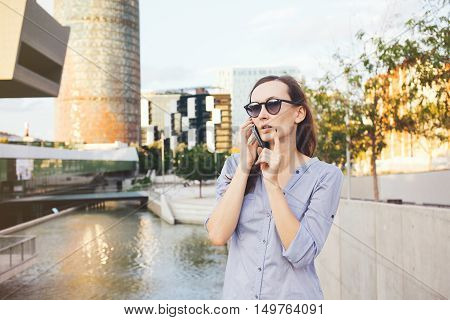 Female broker is talking on the phone with the clients near new modern buildings. Broker woman is standing on the street and having telephone conversation. Rental agents. Broker business