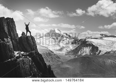 Man with rised hands stands in winner pose on the cliff on background of mountains