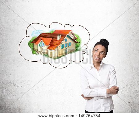 African American girl dreaming about her own house standing near concrete wall. Concept of real estate market.