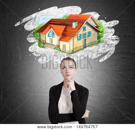 Portrait of young lady dreaming about large house in countryside. Concept of downshifting and abandoning civilization for contemplating and inner peace.