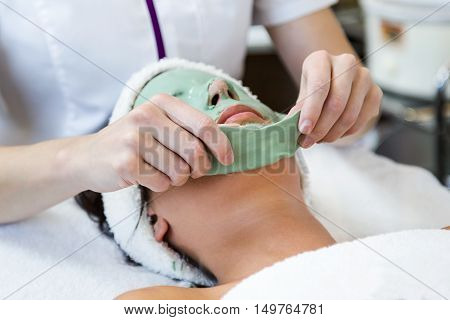 Portrait of beautiful young woman with antiaging facial mask in spa. poster