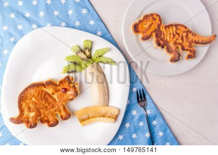 Funny food for kids: Pancake in the form of dinosaurs, supplemented by fruits in the form of palm trees