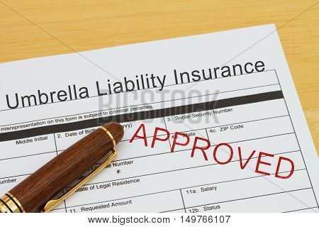 Applying for a Umbrella Liability Insurance Approved Umbrella Liability Insurance application form with a pen on a desk with an approved stamp